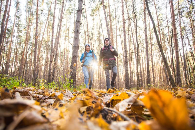 Adventure, travel, tourism, hike and people concept - smiling couple walking with backpacks over autumn natural royalty free stock photography