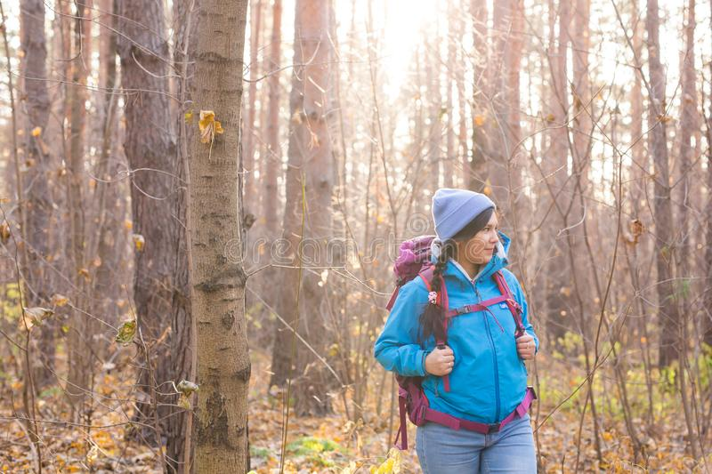 Adventure, travel, tourism, hike and people concept - smiling woman walking with backpacks over natural background royalty free stock images