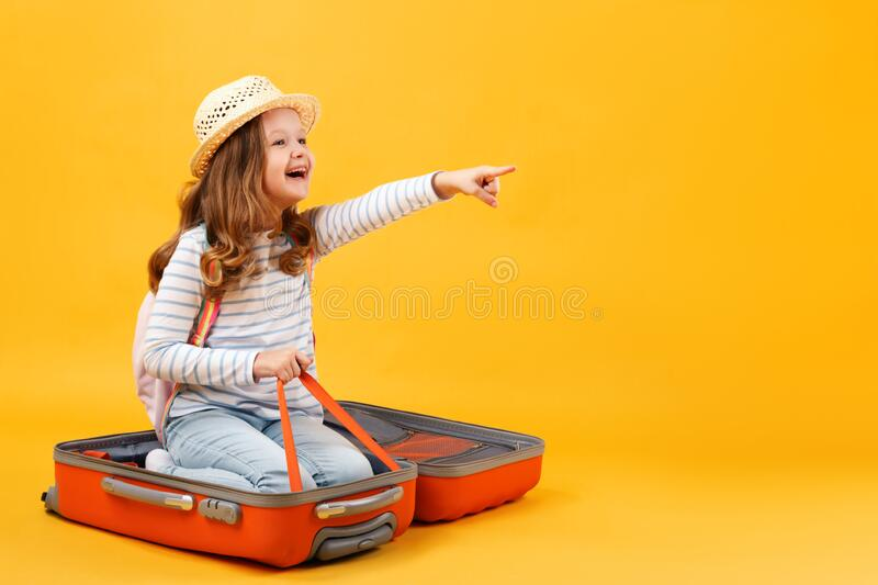 Adventure travel trip dream concept. A cheerful little girl sits inside a suitcase and shows her hand forward. A child on a yellow background in the studio royalty free stock image