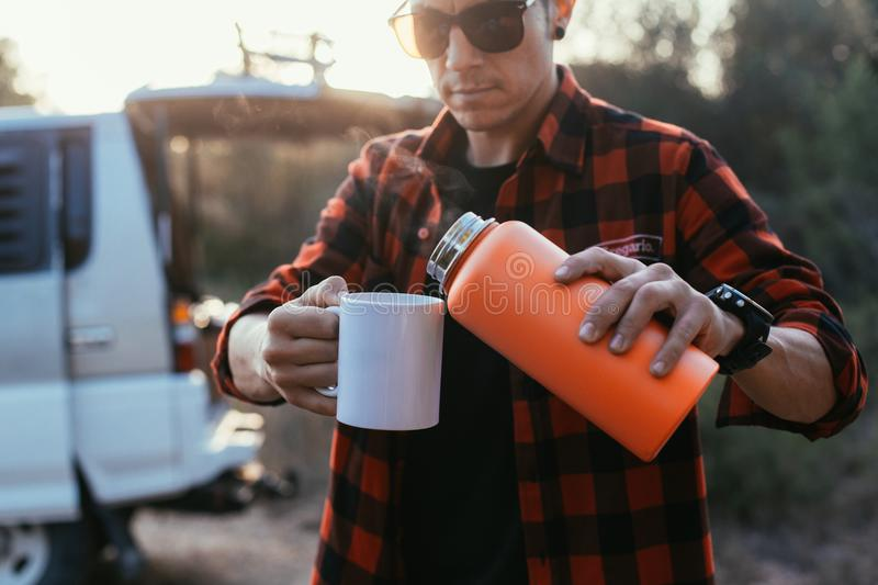 Adventurer tourist pours coffee from thermos. Trendy young man stands on camping site or on road stop in front of his camping van or camper with open trunk royalty free stock photography