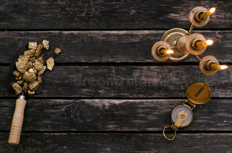 Adventurer. Treasure hunter table. Explorer. Gold ore nuggets in shovel, compass and burning candle on old adventurer table. Goldminer Treasure hunter concept royalty free stock images