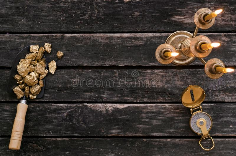 Adventurer. Treasure hunter table. Explorer. Gold ore nuggets in shovel, compass and burning candle on old adventurer table. Goldminer Treasure hunter concept stock images