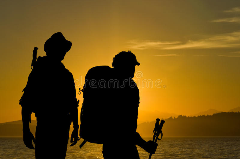 Adventurers. Silhouette of two adventurers admiring the radiant sunset over a lake with hills and forests in the background stock images