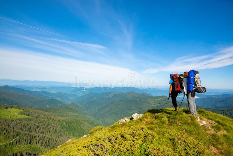 Adventurers with backpacks stands on green mountain ridge. Against background of blue sky and admire panorama of mountains. Epic travel in the mountains. Back royalty free stock photos