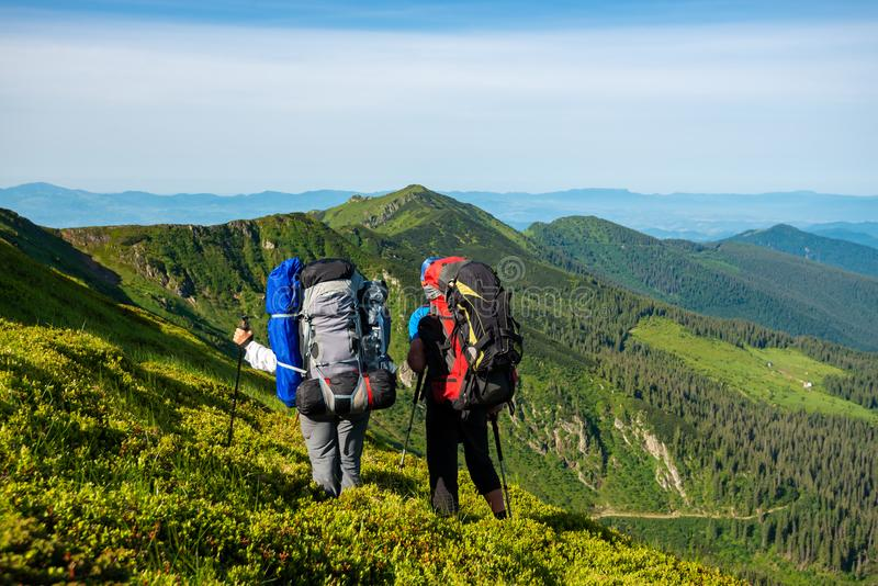 Adventurers with backpacks stands on green mountain slope. And admire panorama of mountains in front of them. Epic travel in the mountains. Back view stock photography