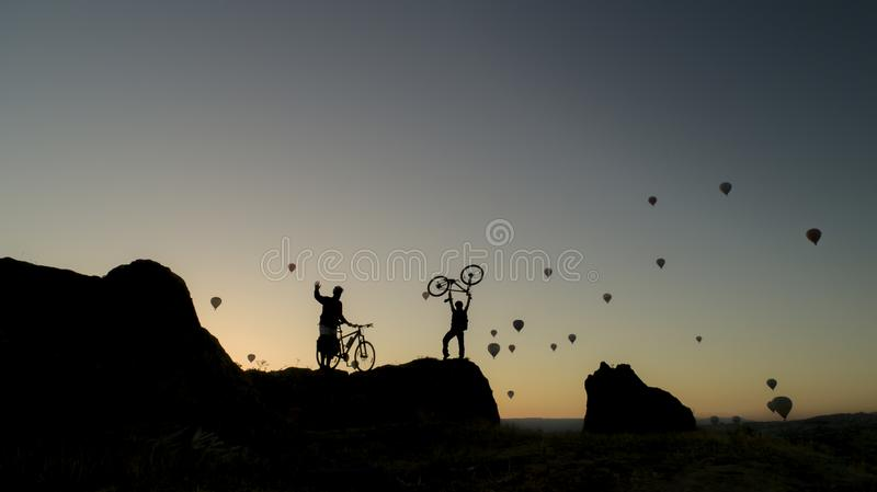 Adventurers exploring by bicycle. Silhouette of two adventurers, one holding his bicycle aloft (above his head) on a rocky promontory, at sunset (or sunrise stock photos