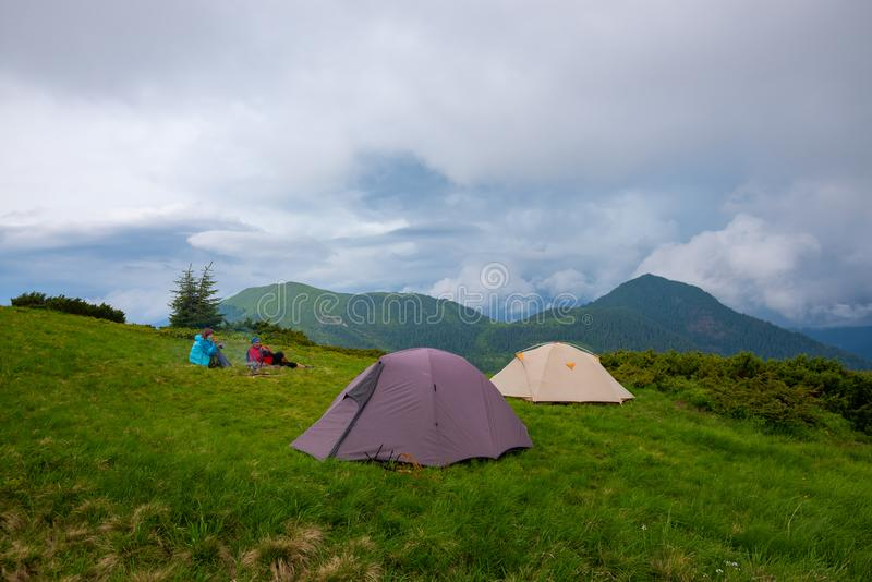 Adventurers rest and drink coffee. Next to tents on the green mountain meadow against the background of wooded hills under low heavy clouds. Epic travel in the royalty free stock photography
