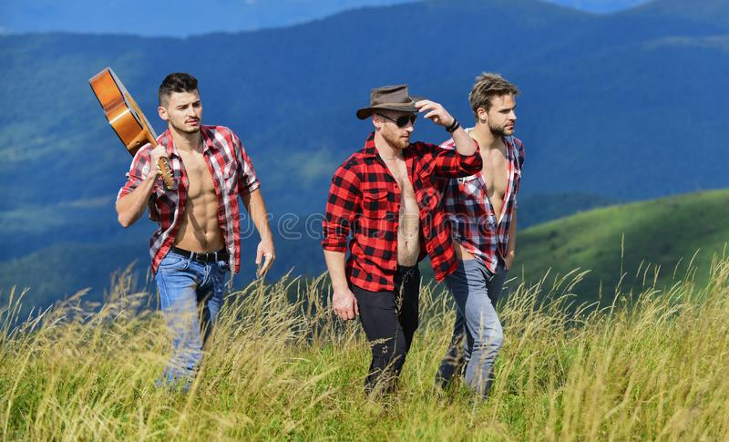 Adventurers squad. Tourists hiking concept. Group of young people in checkered shirts walking together on top of. Mountain. Men with guitar hiking on sunny day royalty free stock photography