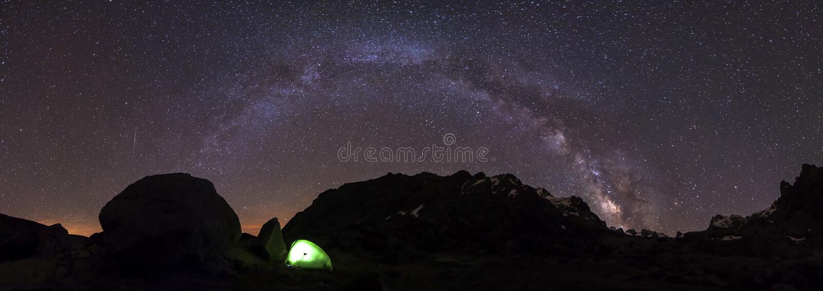 Adventurers will sleep in a million stars hotel in a Bivouac Camping tent under milkyway arch. Panoramic photography shows the complete milkyway arch at night royalty free stock image