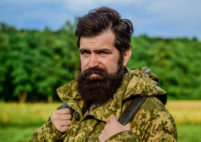 Adventures. brutal male poacher. male beard care. bearded man hiking with backpack. mature hipster with beard in. Military jacket. Hunter man. Hunting season stock images