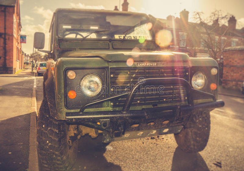 Adventures by car - Land Rover. Leamington Spa, West Midlands, United Kingdom - January 30, 2016: Green Land Rover Defender parked at the street in a sunny day royalty free stock photography