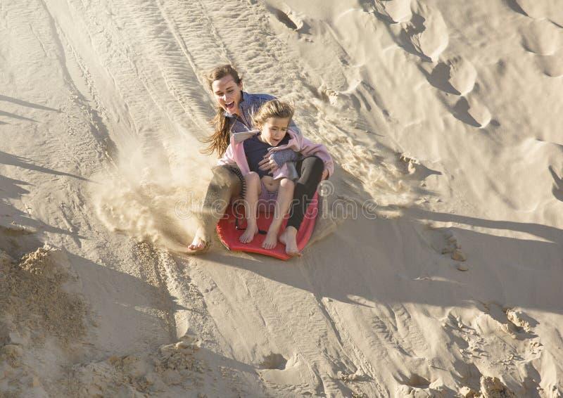 Adventuresome девушки всходя на борт вниз с песчанных дюн стоковое фото rf