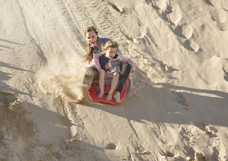 Adventuresome girls boarding down the Sand Dunes. Brave and adventuresome Girls boarding and sliding down the Sand Dunes. They are taking a courageous plunge royalty free stock photo