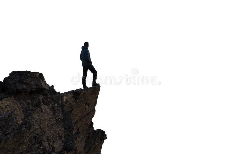 Adventurous Man Hiker With Hands Up on top of a Steep Rocky Cliff. Adventurous Man Hiker Standing on top of a Steep Rocky Cliff. White Background Isolated Cutout royalty free stock image