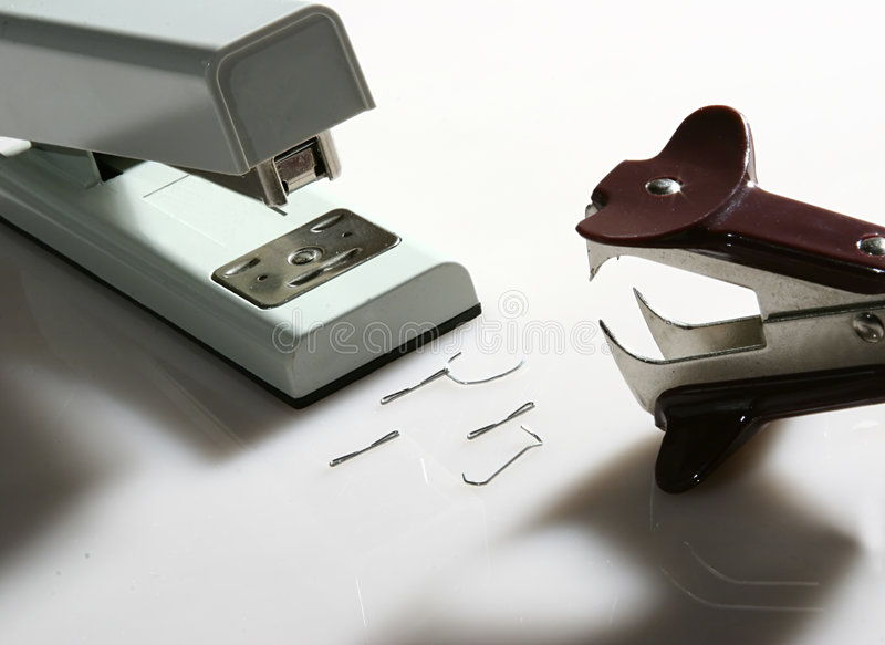 Adversaries 3. Confrontation between a stapler and a staple remover. Metaphor stock photography