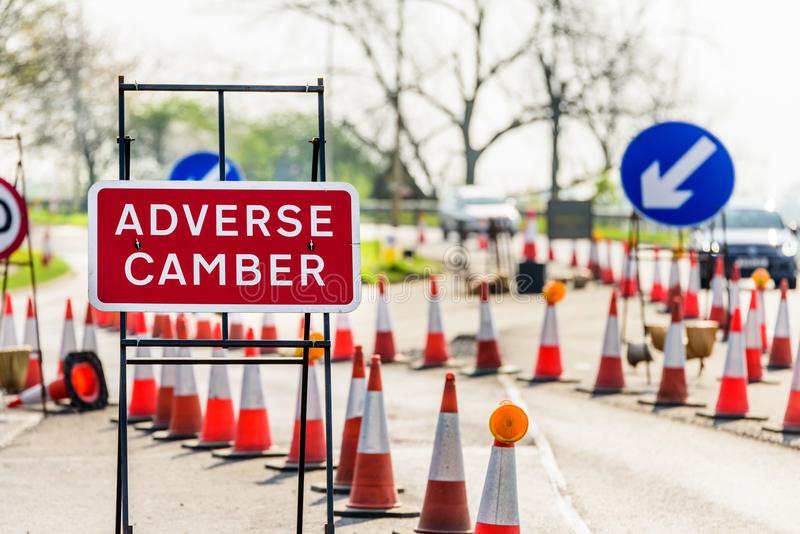 Adverse Camber Roadworks sign on UK motorway with cones.  stock photos
