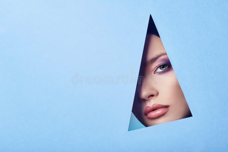 Adverterend de Mooie mollige perfecte ogen van de lippen heldere roze kleur, kijkt de vrouw in gat gekleurd blauw document, schoo royalty-vrije stock afbeelding