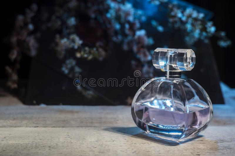 Adverterend women's parfum Flessenglas op houten lijst aangaande bloemen donkere achtergrond royalty-vrije stock fotografie