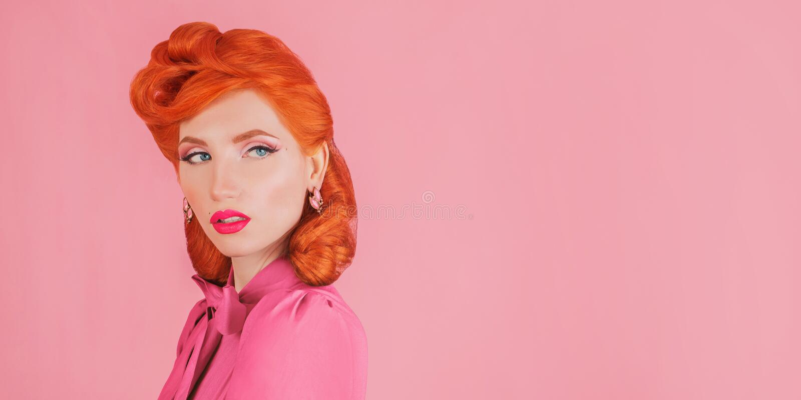 Advertise cosmetics. Woman in pink retro dress. Minimal colorful trend in design. Redhead model with red lips advertise cosmetics stock photos