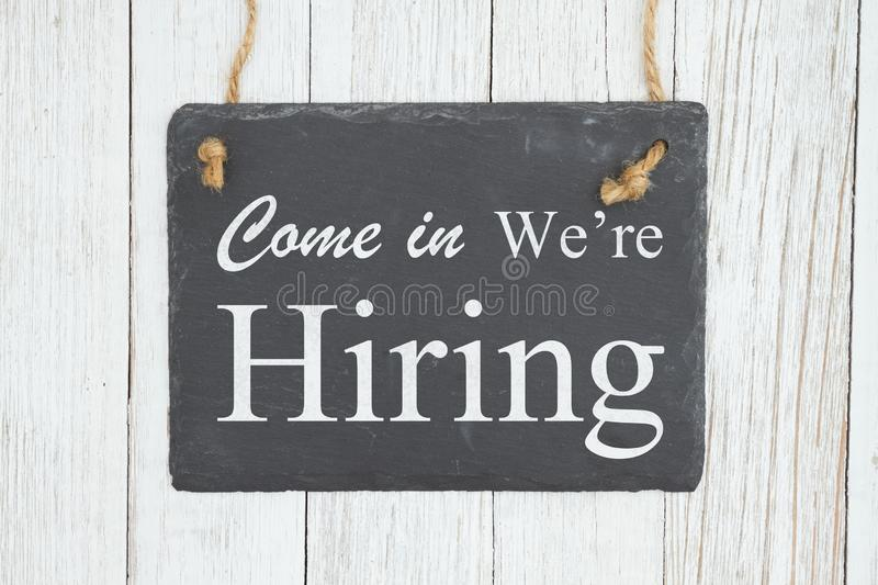 Come in we`re hiring text on a hanging chalkboard on weathered whitewash textured wood royalty free stock images