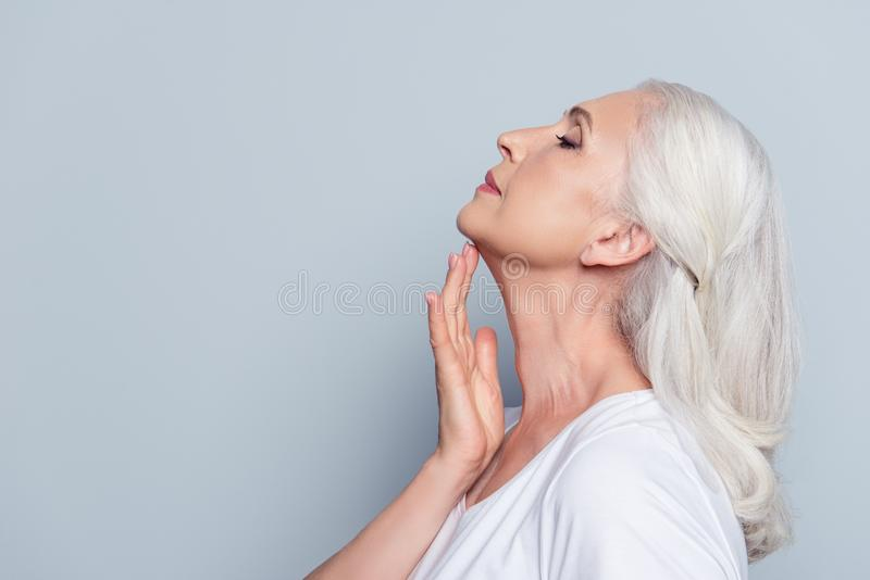 Advertisement concept. Close up profile with copy space of nice, charming, aged woman, touching her skin of neck with hand over g royalty free stock photo