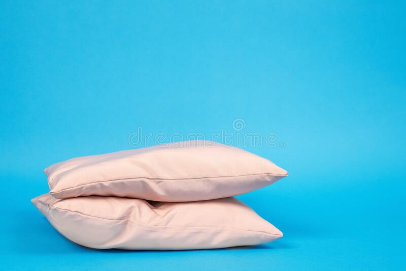 Advertisement of ergonomic pillows filled with feathers, memory foam or polyester without pillowcases stacked on blue background. Front view, copy space for stock photo