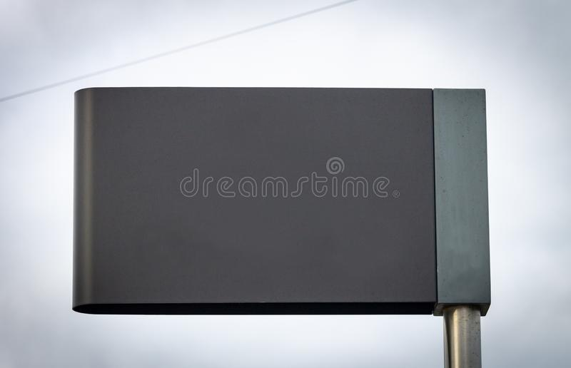 Advertisement Mockup Street Sign - Grey. Grey Street Sign Advertisement Mockup. Copy Space. Iron Pole. Cloudy Background royalty free stock photo