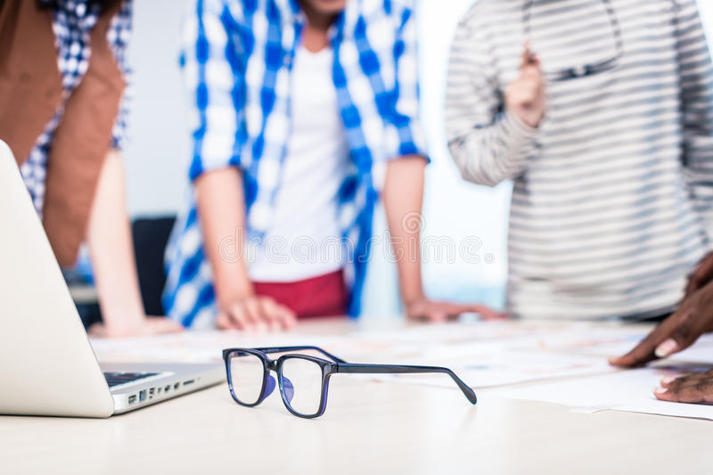Advertising agency team in creative meeting. Focus on glasses in foreground royalty free stock photo