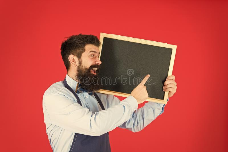Advertising concept. great cuisine. cooking by recipe. welcome. Restaurant or cafe advertising. bearded hipster cook in. Apron. happy man chef with blackboard stock photo