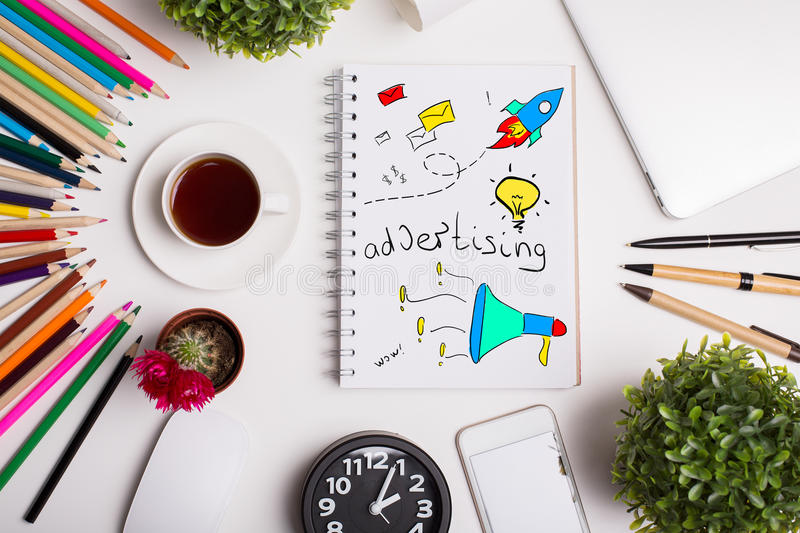 Advertising concept. Top view of modern office workplace with colorful supplies, coffee cup, plants and notepad with creative sketch. Advertising concepty royalty free stock photos