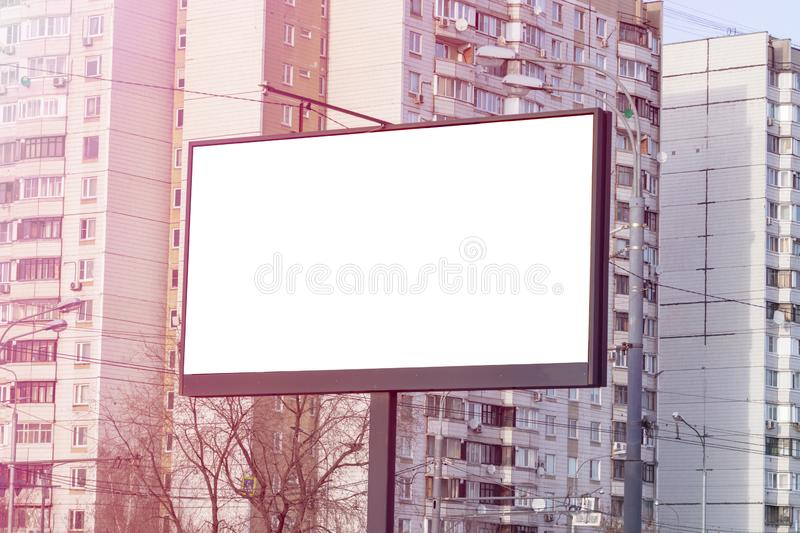 Advertising concept, white empty billboard in the city, apartment buildings on background, copy space stock images