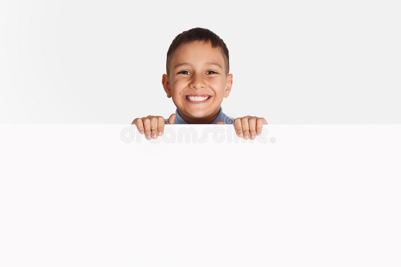 Advertising. Little kid standing behind blank banner. On light background royalty free stock photos