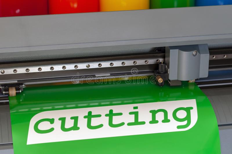 Advertising services for plotter cutting vinyl film. Cutting plotter close-up. The process of cutting a vinyl film stock image