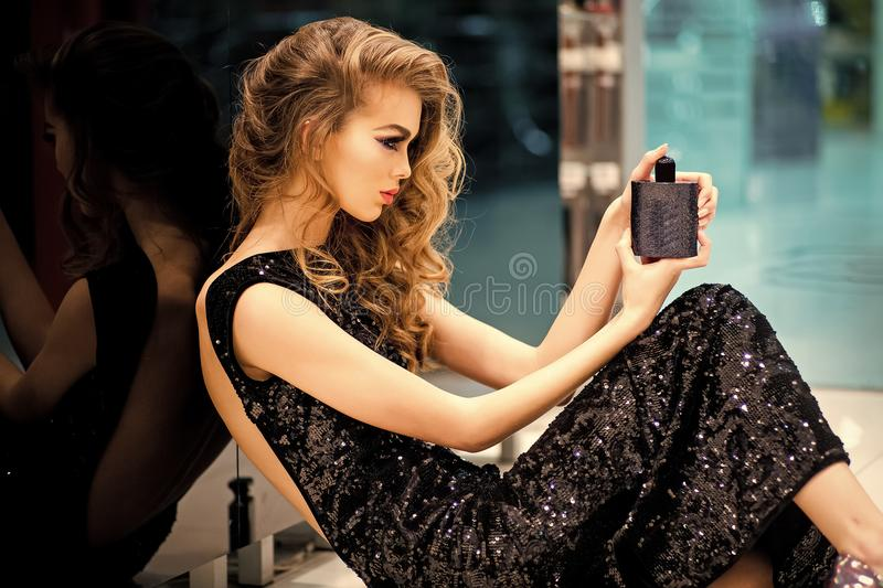 Advertising women`s perfume. Young woman with bottle of perfume royalty free stock photos