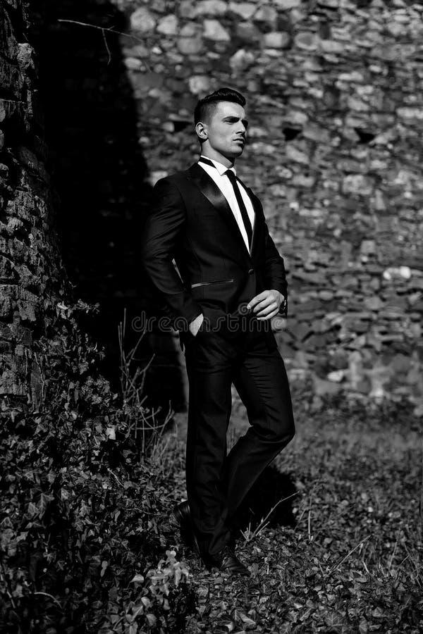 Advertizing av dräkter för man` s Den unga mannen poserar utomhus- royaltyfri foto