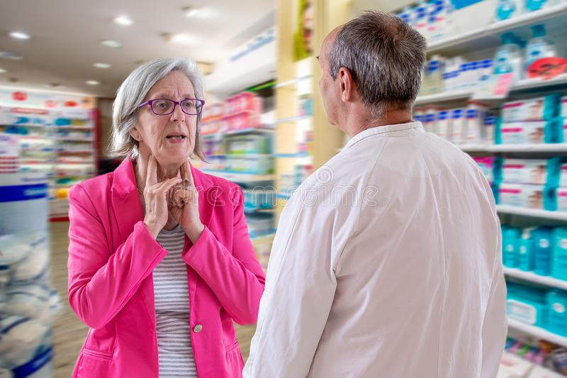 Advice and conultancy concept: pharmacist is talking to a client at the pharmacy, men is having a sore throat stock images