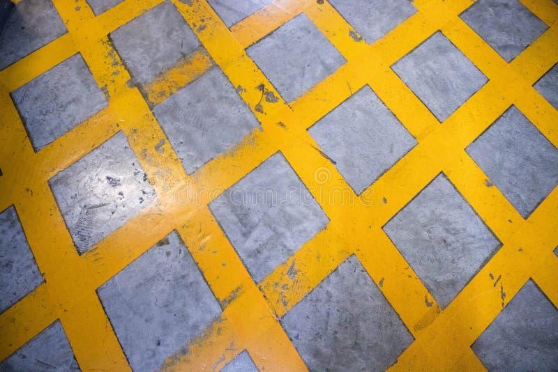 Advierta la muestra, rayas peligrosas, trayectoria amarilla en área del parking imágenes de archivo libres de regalías