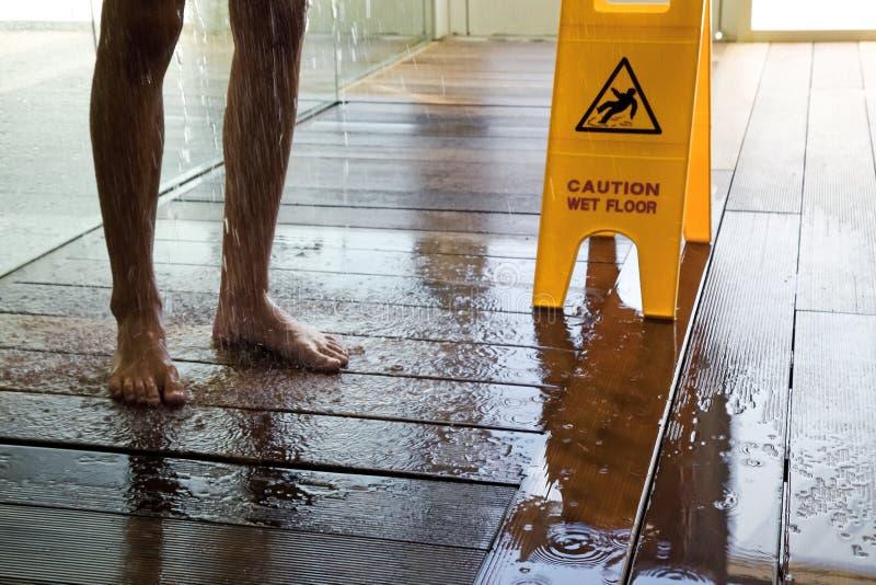 Advirta o sinal molhado do assoalho ao lado do homem que toma o chuveiro imagem de stock
