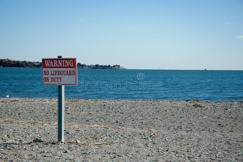 Advirtiendo, ningún salvavidas On Duty Sign en la playa imagenes de archivo