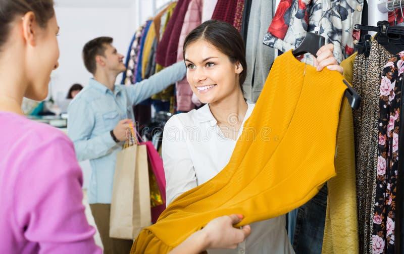 Adviseur die de kleren van de klantenherfst in winkel aanbieden royalty-vrije stock afbeelding