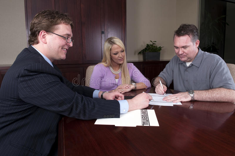 Advisor reviewing contract with clients stock images