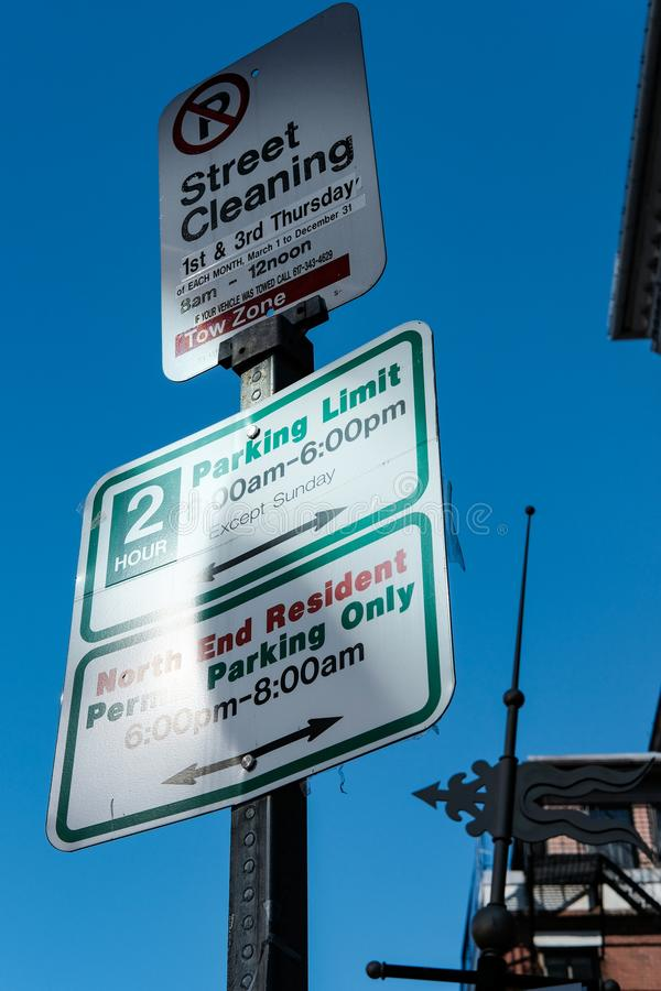 Parking and resident signs seen on a US city lamppost. The advisory signs show permit area parking, parking limits and street cleaning information signs, seen stock photo