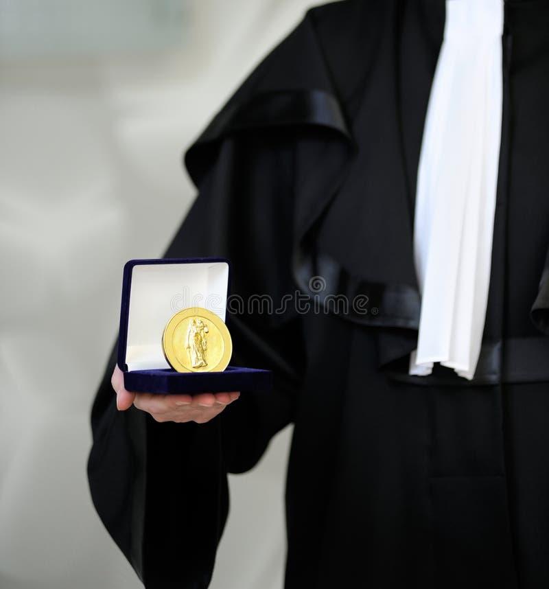 Advocaat die een robe draagt die rechtvaardigheidsMEDA houdt stock afbeeldingen