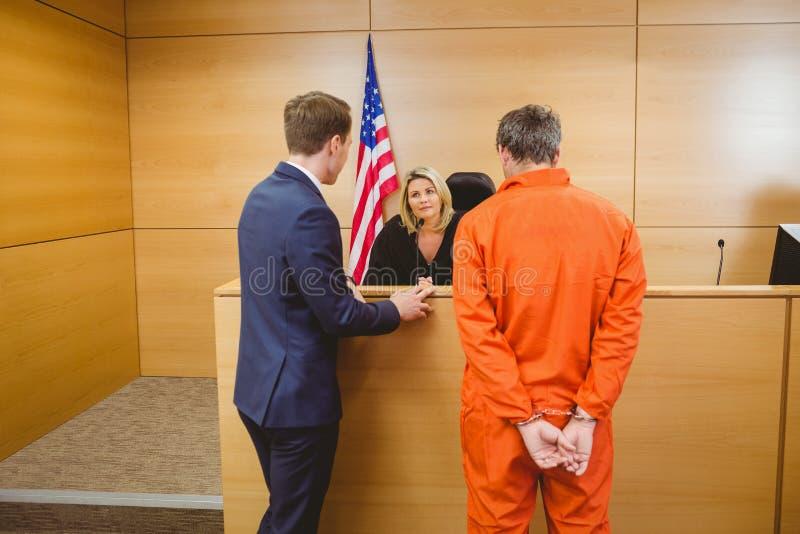 Advocaat en rechter die naast de misdadiger in handcuffs spreken royalty-vrije stock fotografie