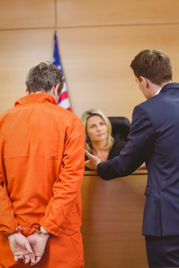 Advocaat en rechter die naast de misdadiger in handcuffs spreken stock fotografie
