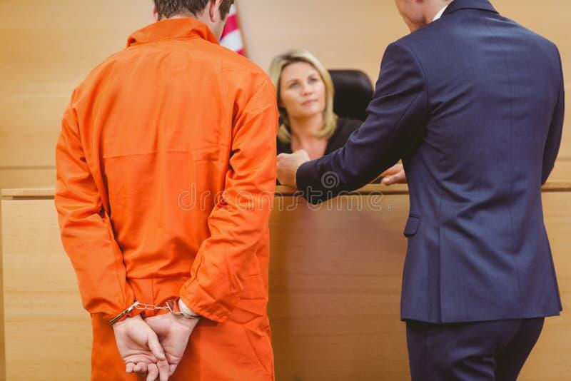 Advocaat en rechter die naast de misdadiger in handcuffs spreken stock foto's