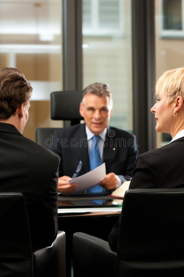 Advocaat of notaris met cliënten in zijn bureau stock afbeelding