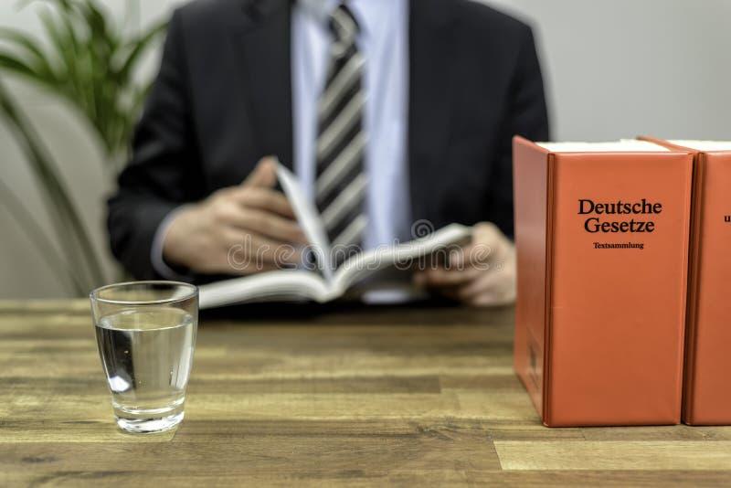 Advocaat in zijn bureau met boeken royalty-vrije stock foto