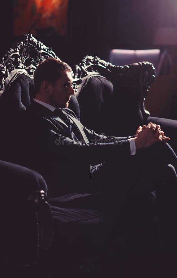 Advogado com a cara não barbeado séria O homem de negócios senta-se no sofá elegante do vintage e pensa-se Sucesso profissional,  imagens de stock