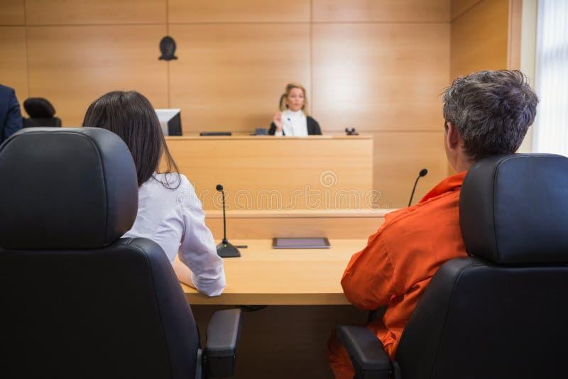 Advogado e cliente que escutam o juiz foto de stock